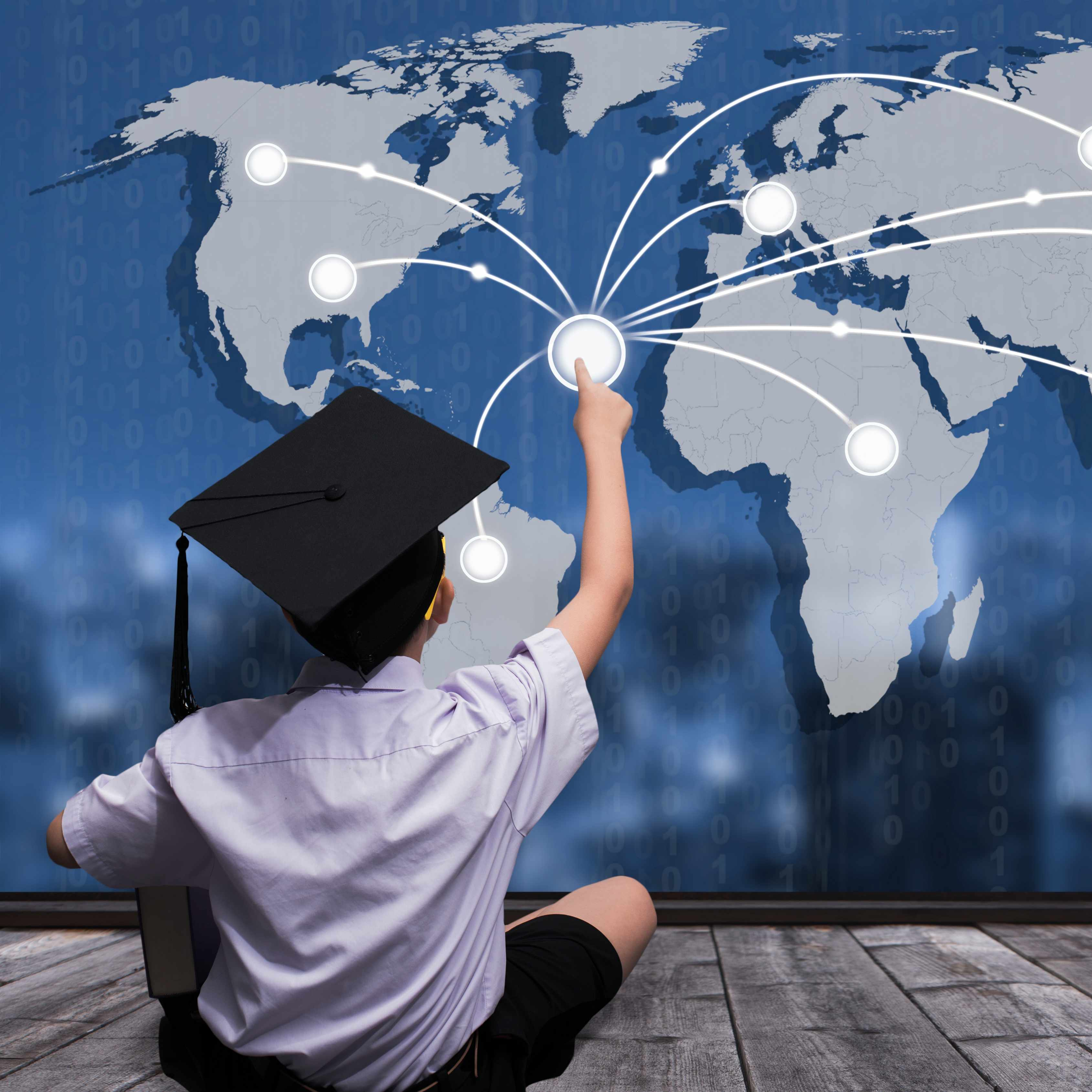 a young boy with a graduation cap sitting in front of a global map