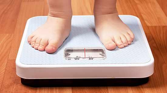 Unos pies infantiles sobre una balanza