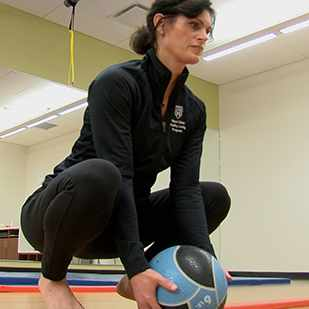 woman squatting with ball at elements of movement class