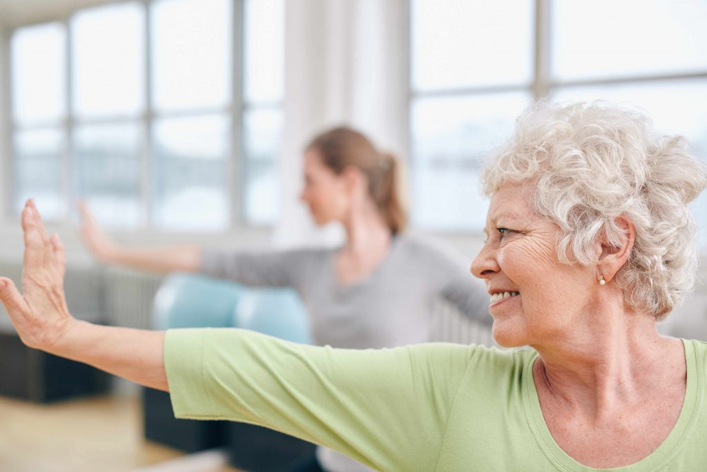 a close-up of a smiling older woman doing stretching exercises in a gym