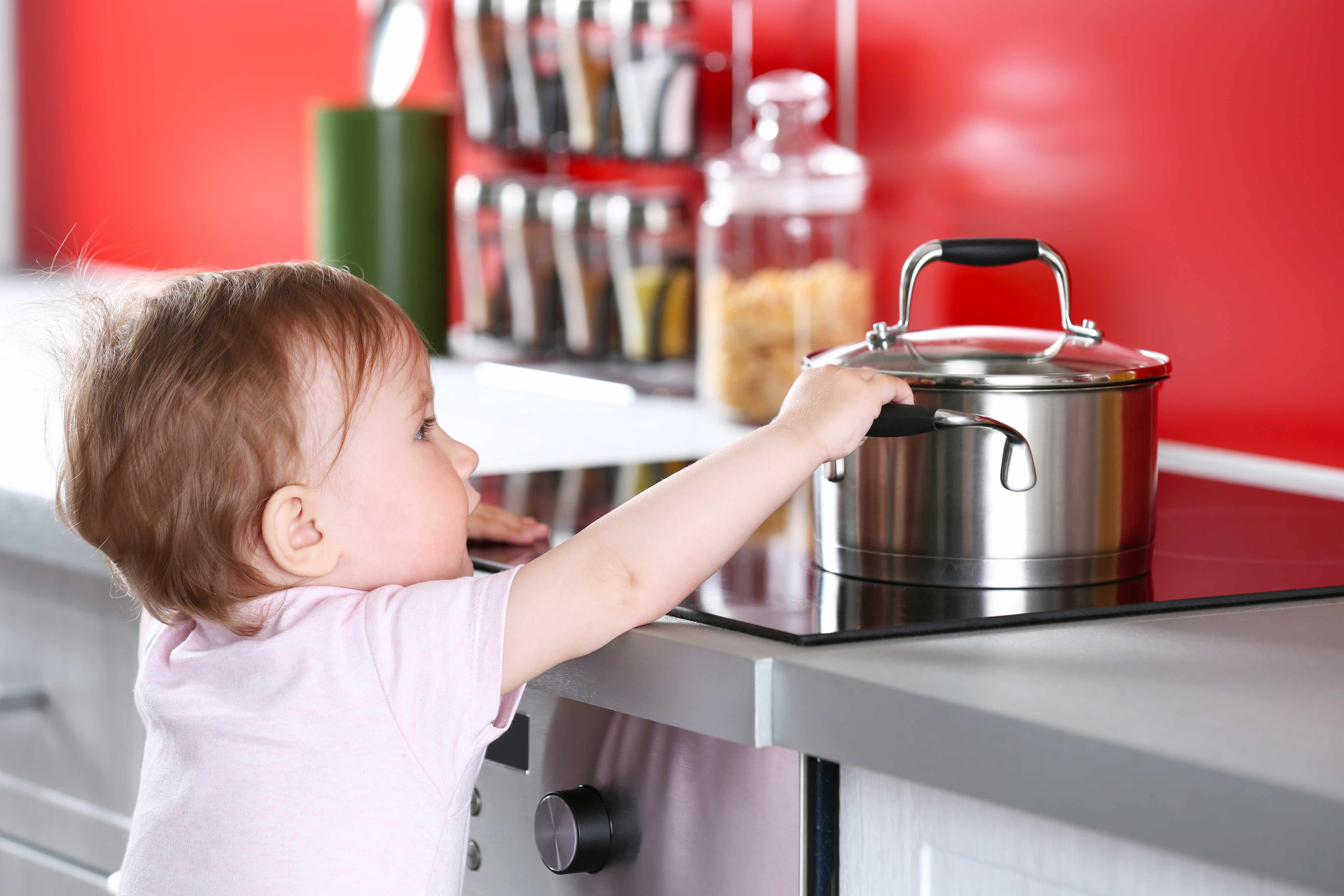 a child reaching on top of a stove for a hot pot risking a burn