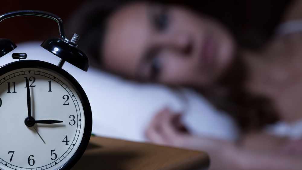 Acercamiento de un reloj despertador que muestra las 3 de la mañana y en el trasfondo aparece difusamente una mujer con la cabeza en la almohada y completamente despierta, víctima del insomnio