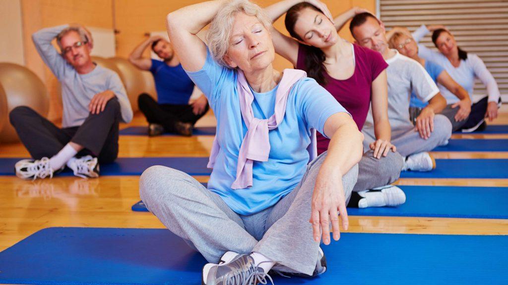 Un grupo de personas, jóvenes y viejas, hombres y mujeres, sentados sobre esteras de yoga en un gimnasio y estirándose