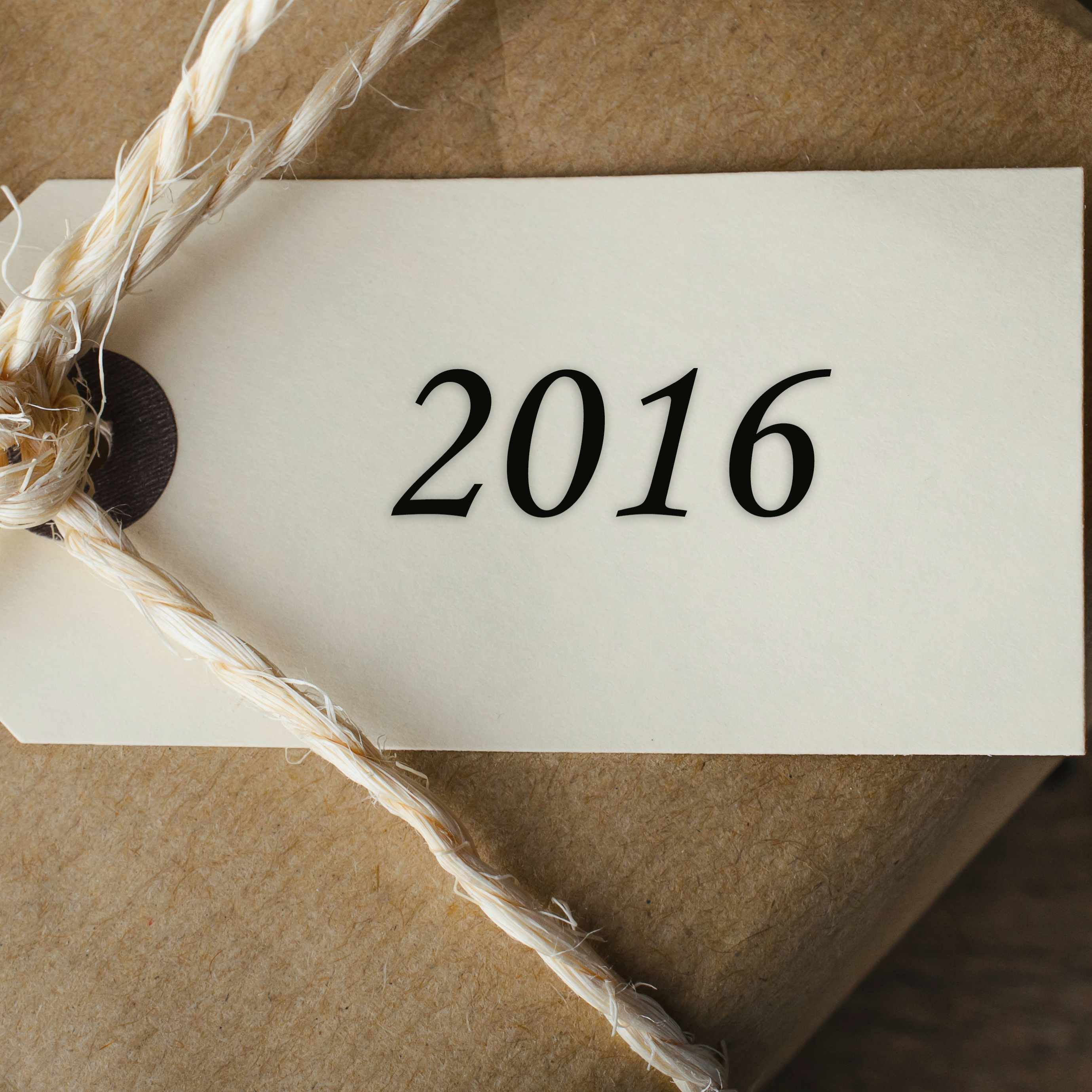a package wrapped in brown paper and string with a '2016' gift tag