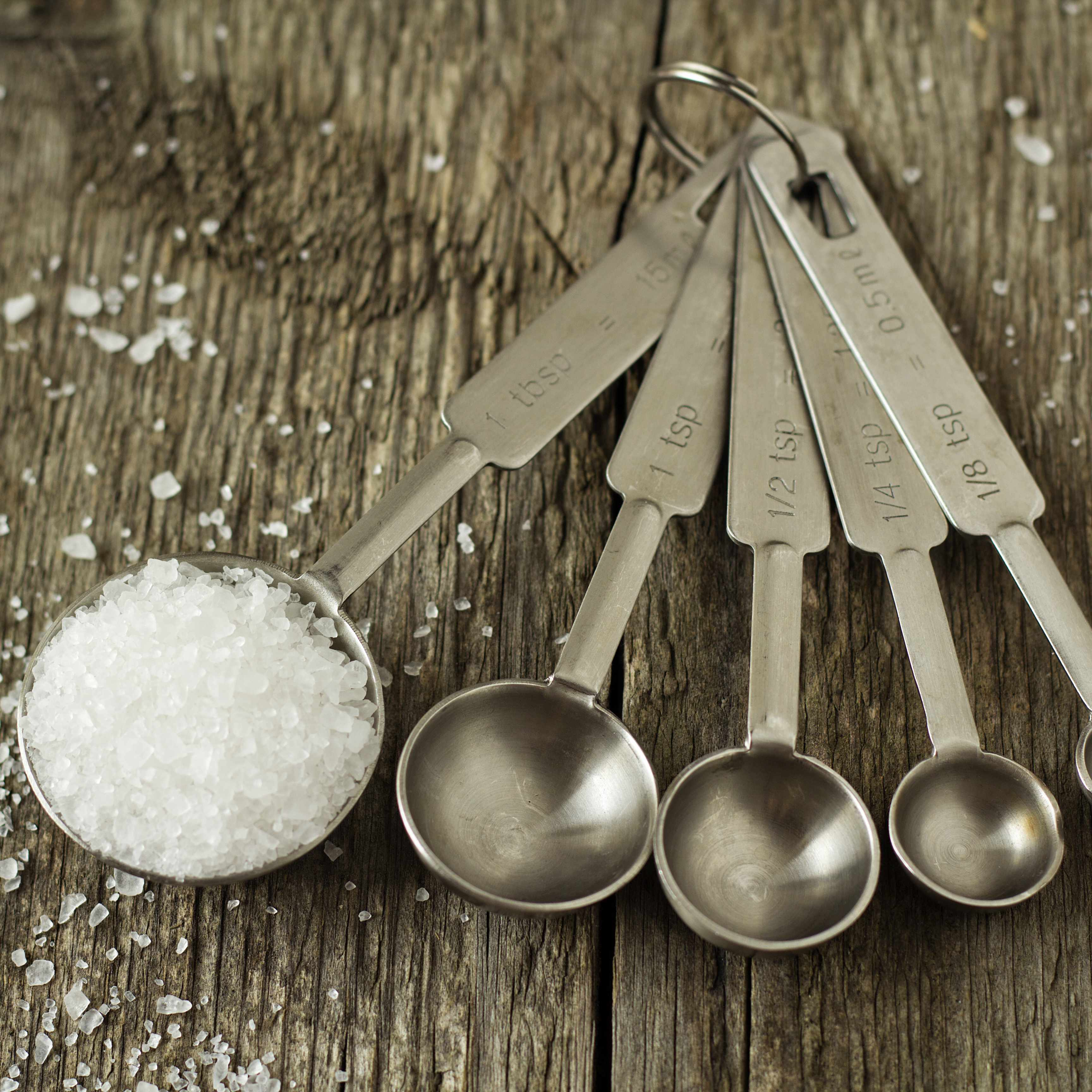 a set of silver measuring spoons on a rough wooden surface, the largest filled with salt spilling over the edges