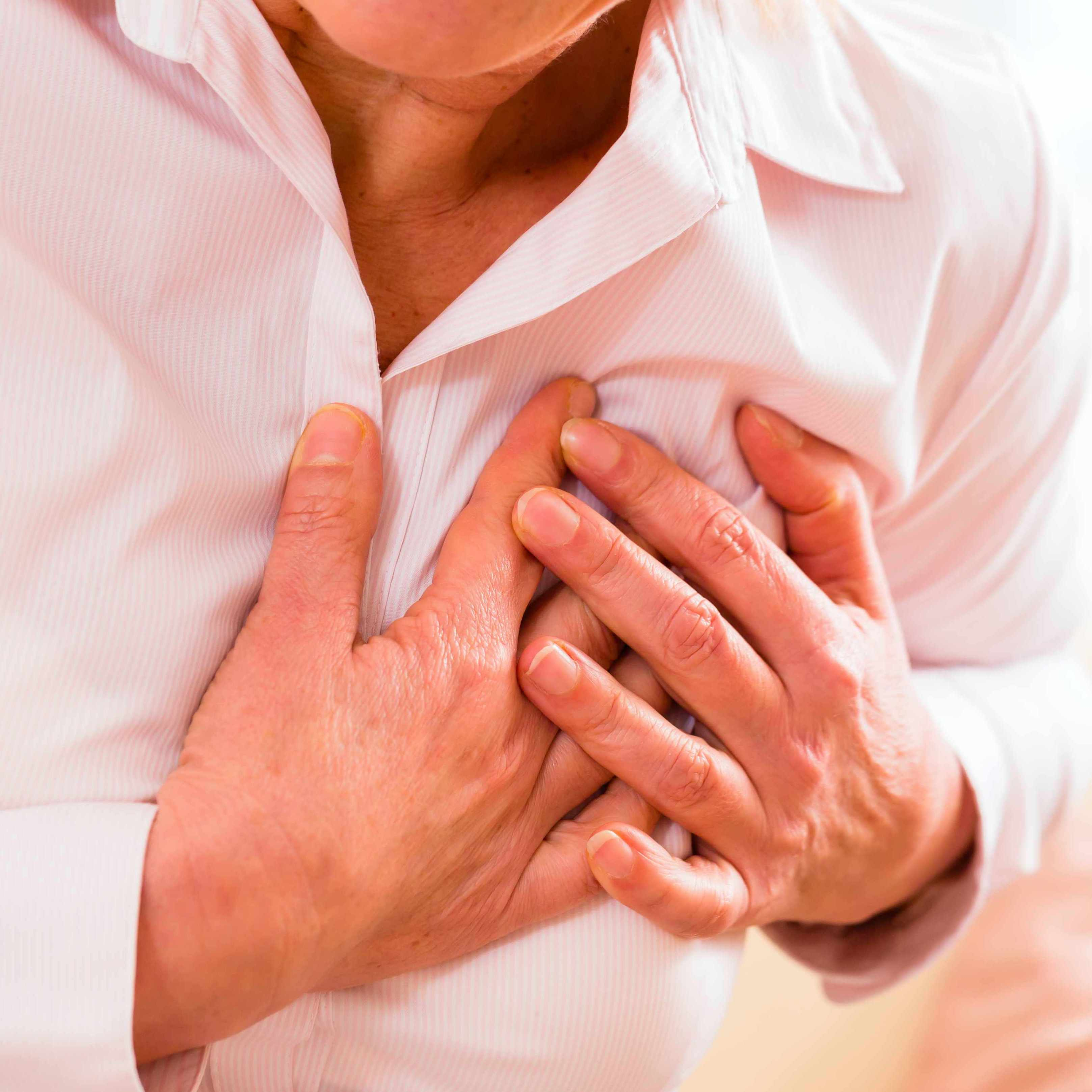 a woman in a pink blouse clutching her chest as if in pain or having a heart attack