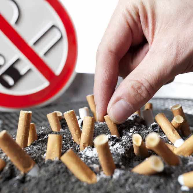 an ashtray full of cigarette butts in front of a no-smoking sign, with a hand shoving another butt into the pile