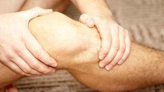 Acercamiento de la rodilla de un hombre, que la sostiene con ambas manos como si le doliera