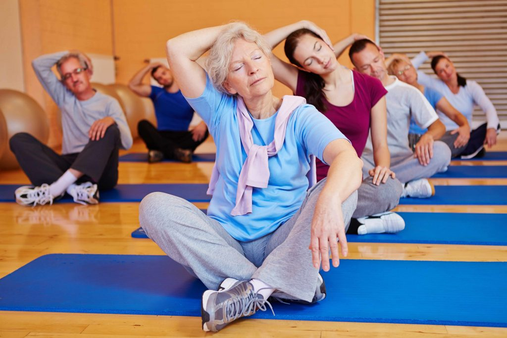 a group of people - young and old, women and men - sitting on yoga mats in a gym, stretching