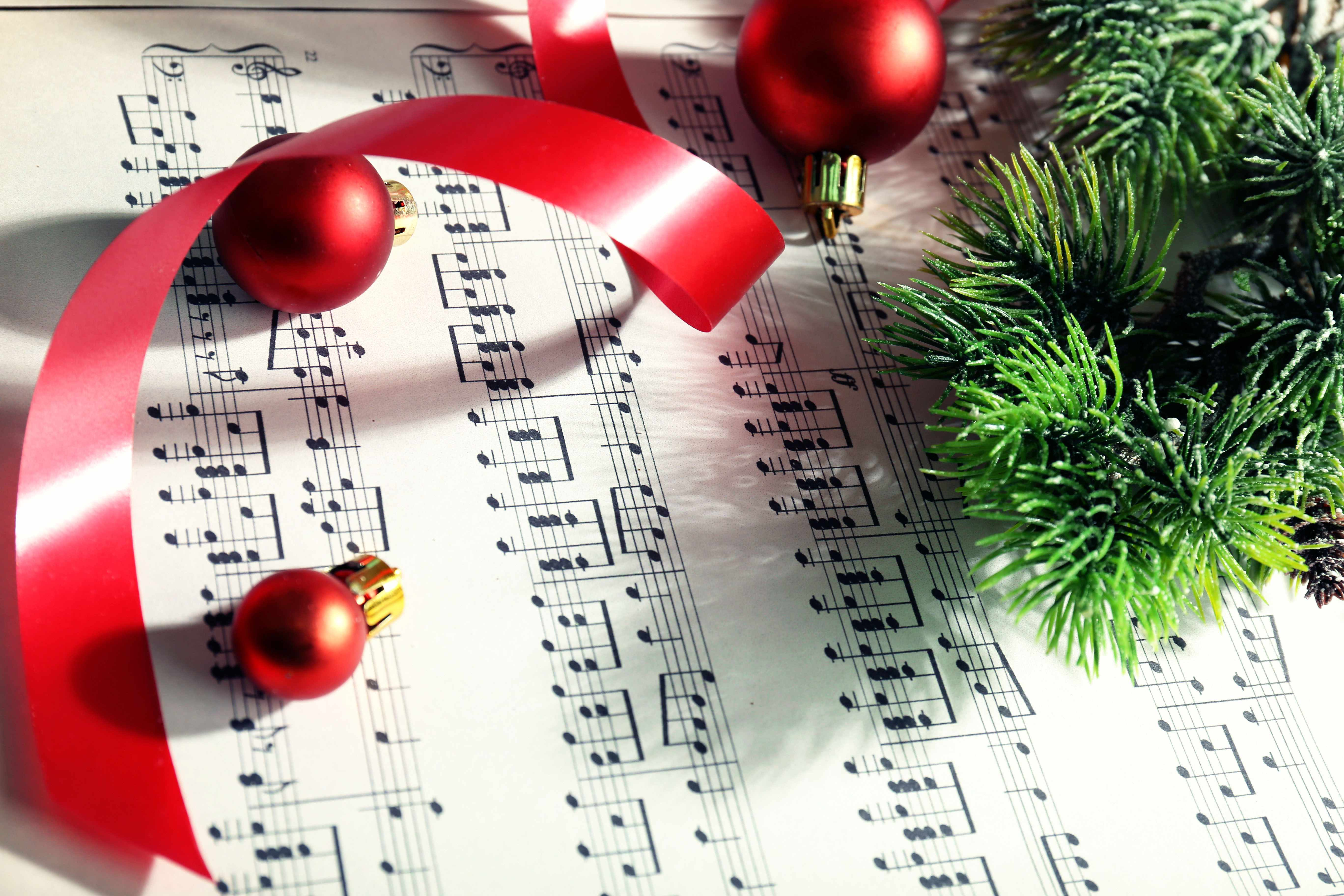 sheet music with holiday ornaments, ribbons and evergreen branches