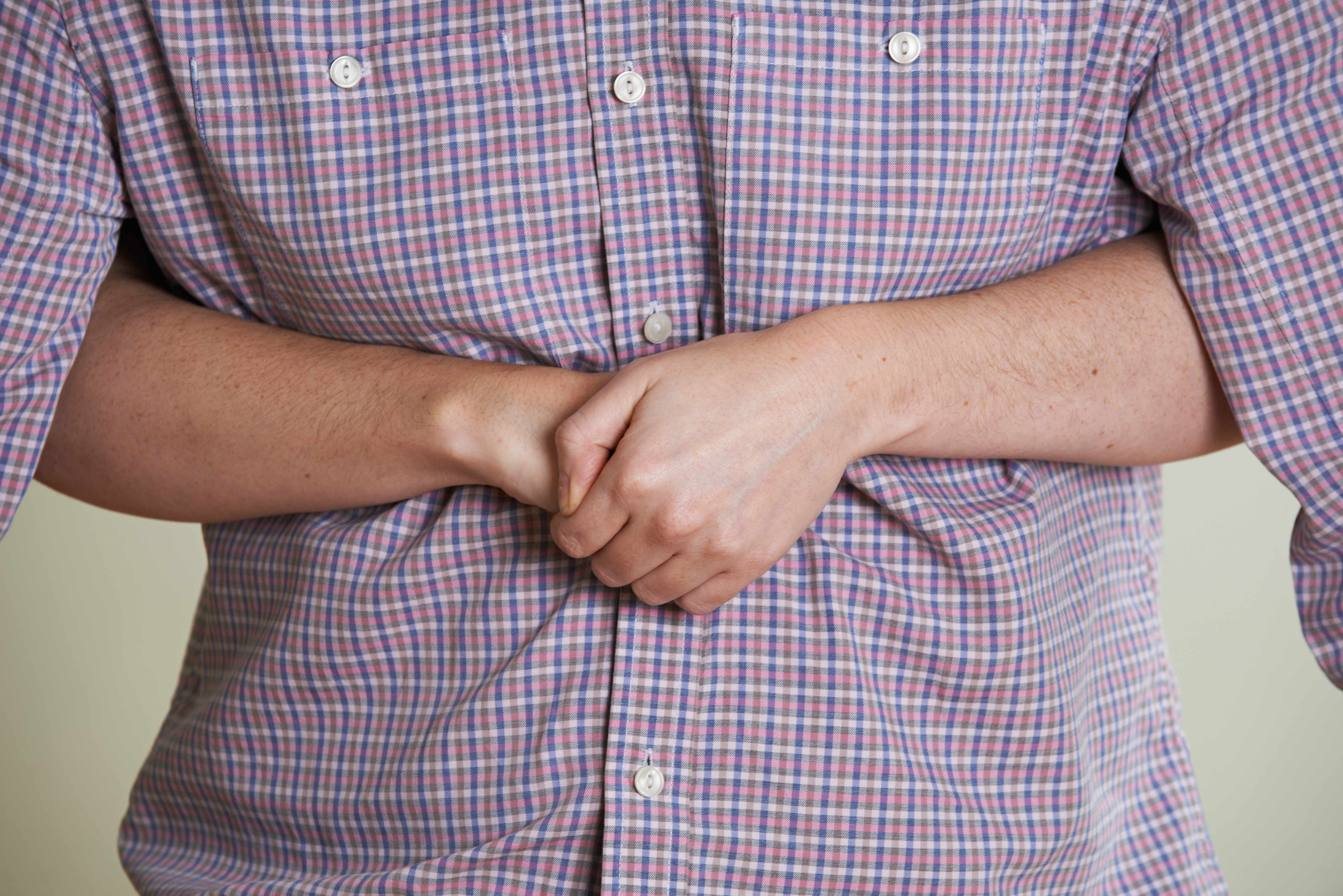 a person with arms wrapped from behind another person doing the Heimlich Maneuver