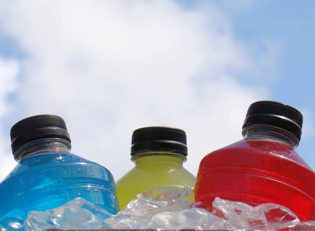a group of sports energy drinks in a cooler of ice cubes with blue sky in the background