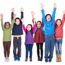 a group of children standing in a line, all smiling and with their arms upraised
