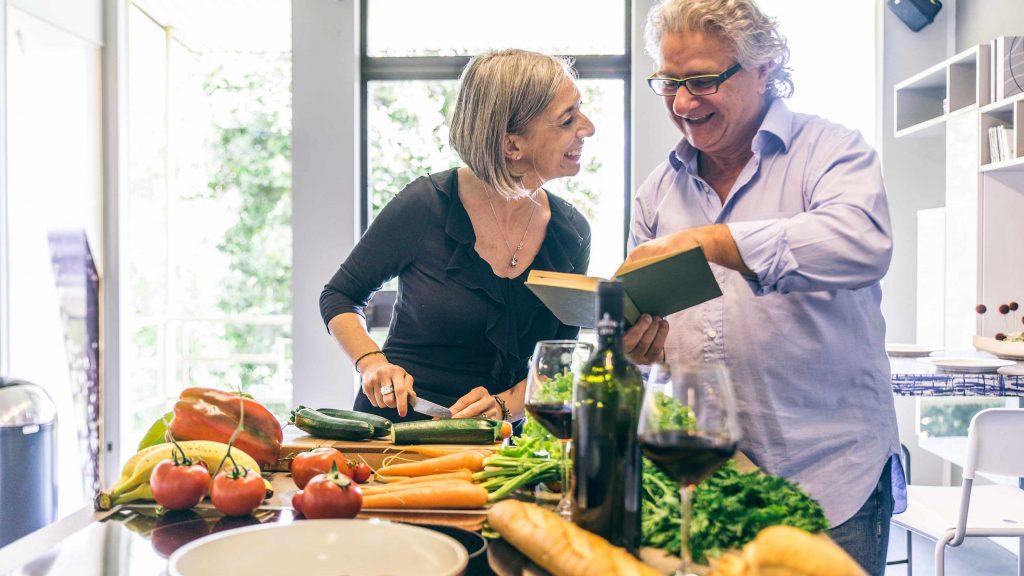 Una pareja de mediana edad sonríe y cocina en conjunto, mientras hay muchas frutas y verduras diseminadas sobre la barra de la cocina