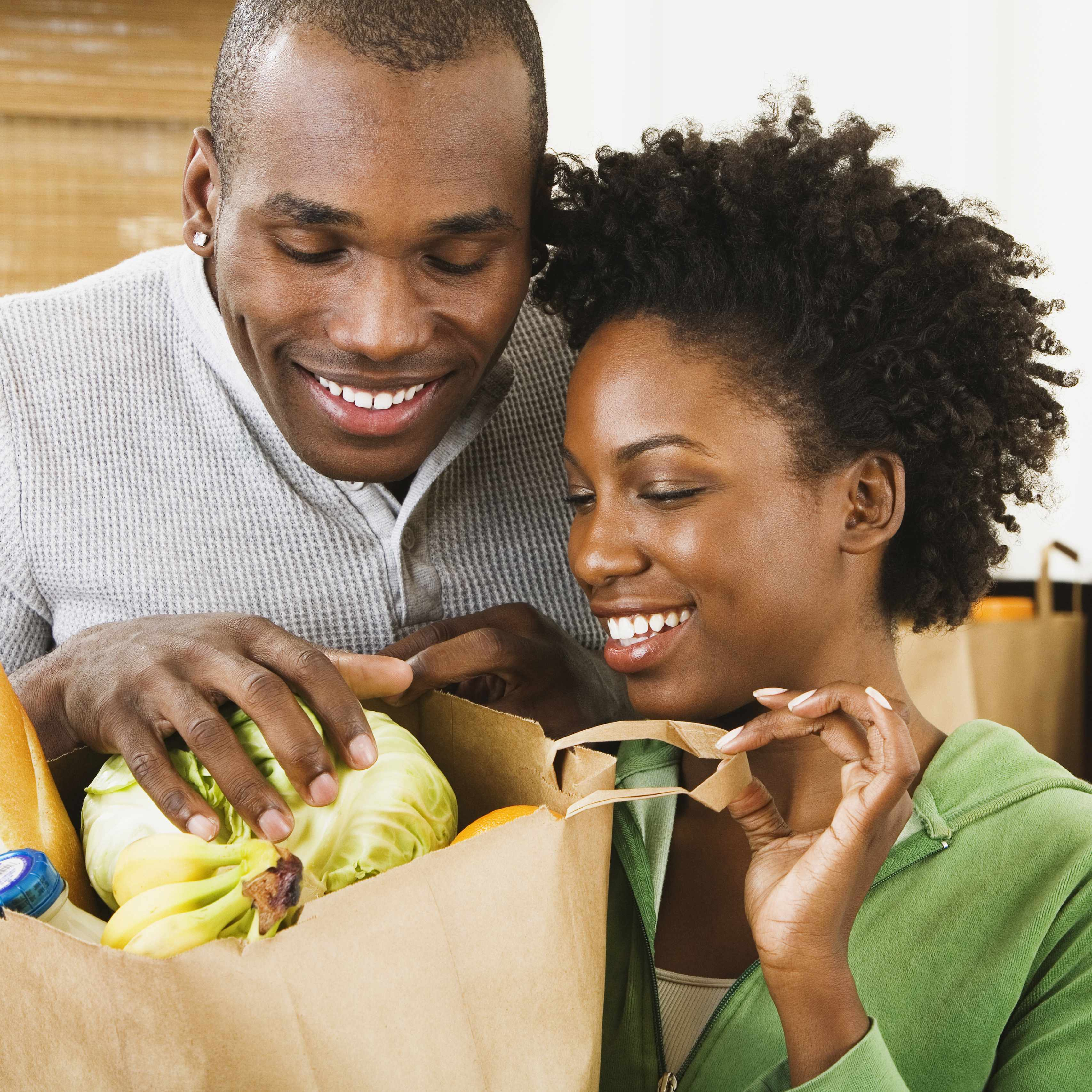 a smiling young couple in their kitchen, looking into a bag of groceries