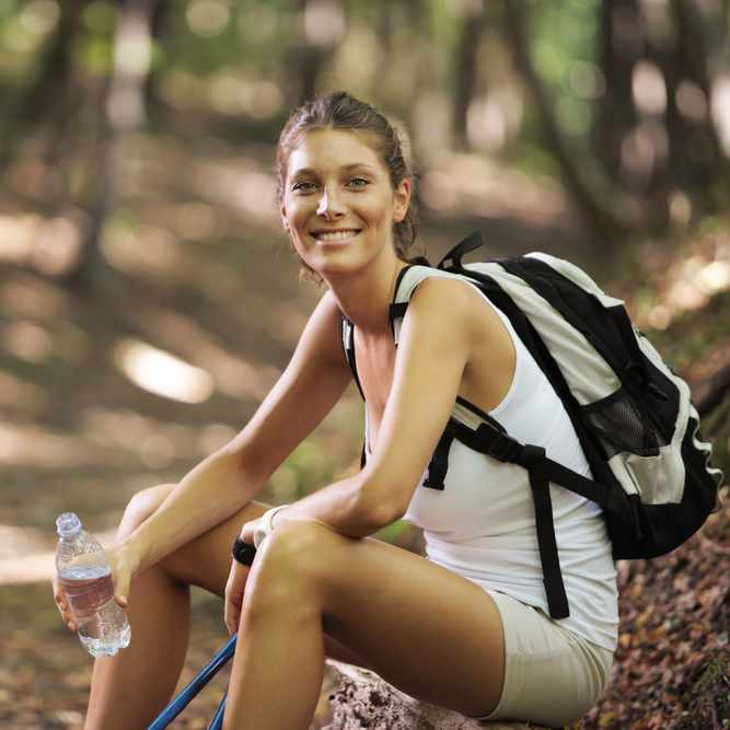 a smiling young woman seated outdoors, taking a break from walking