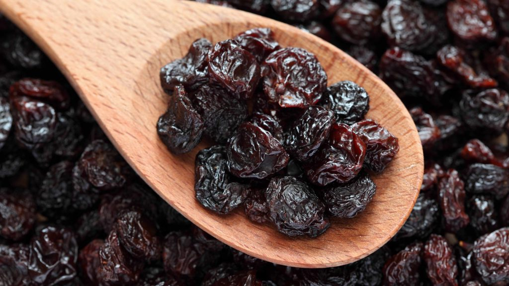 a wooden spoon full of healthy raisins