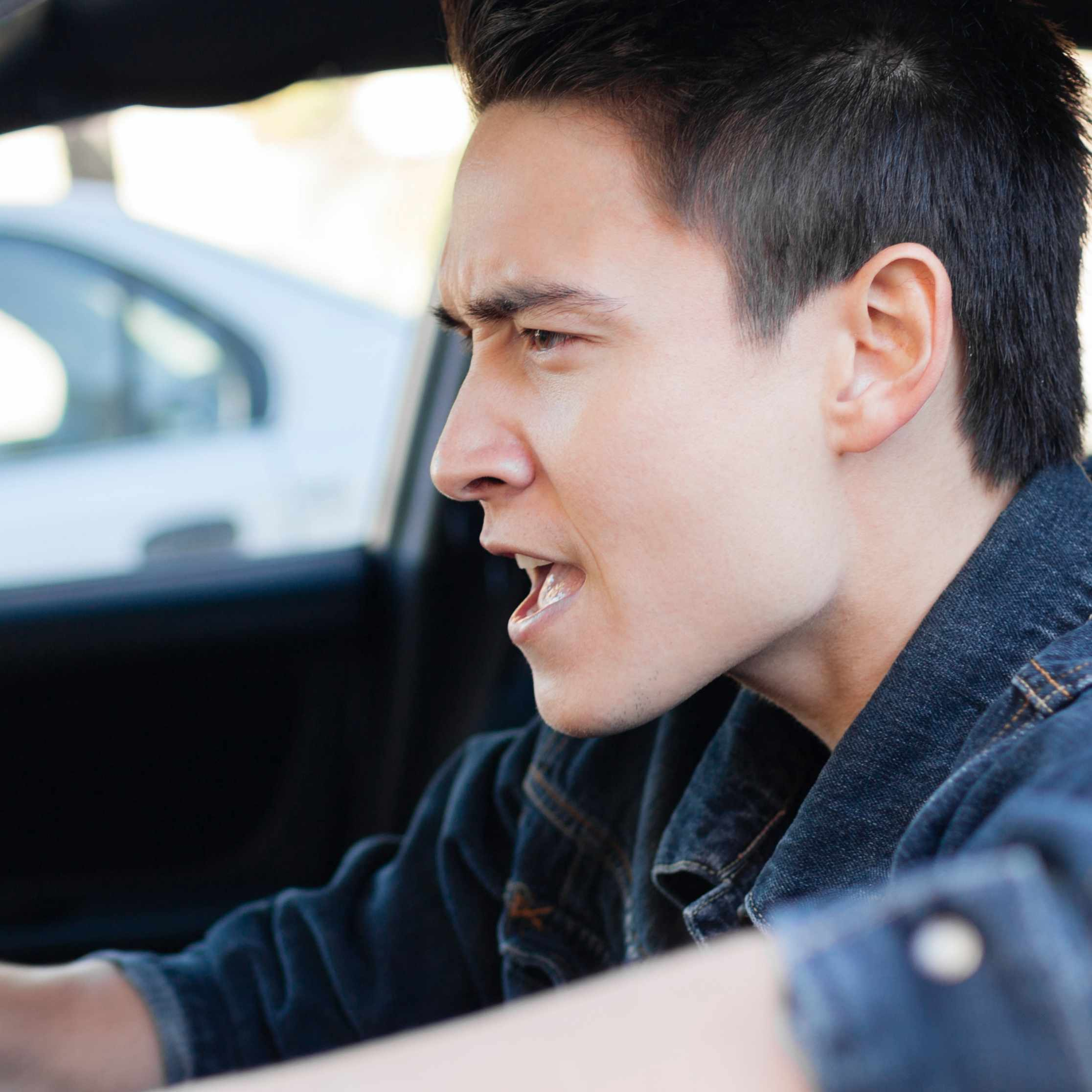 a young, angry man driving in a car demonstrating road rage behind the wheel