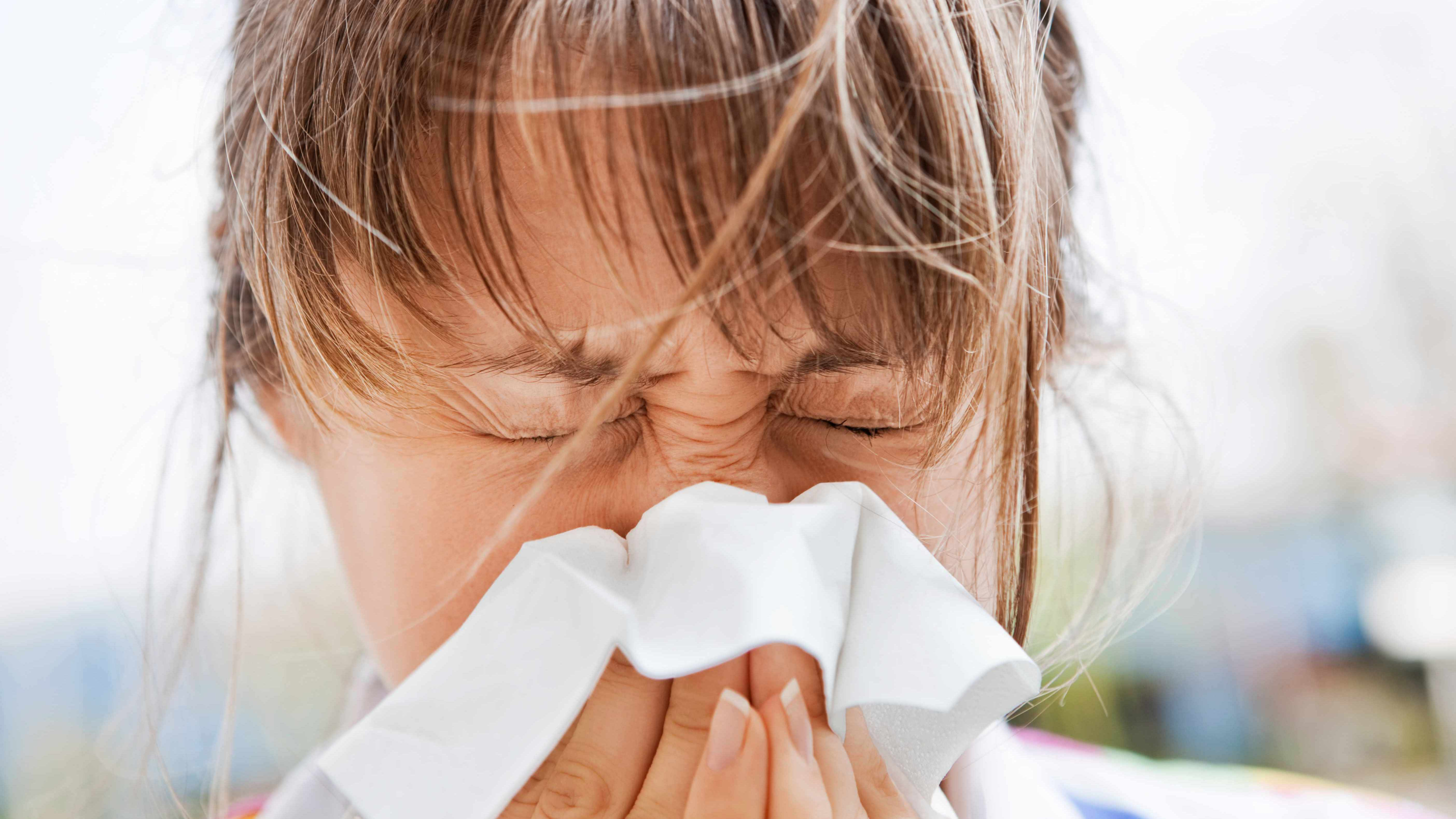 a young woman with a cold or allergies, sneezing into a tissue