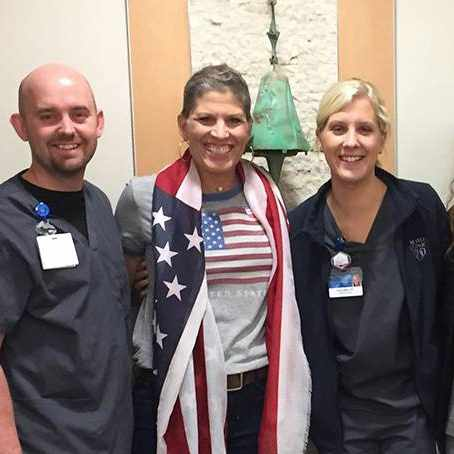 cancer patient sandy morse with staff members standing by the treatment bell