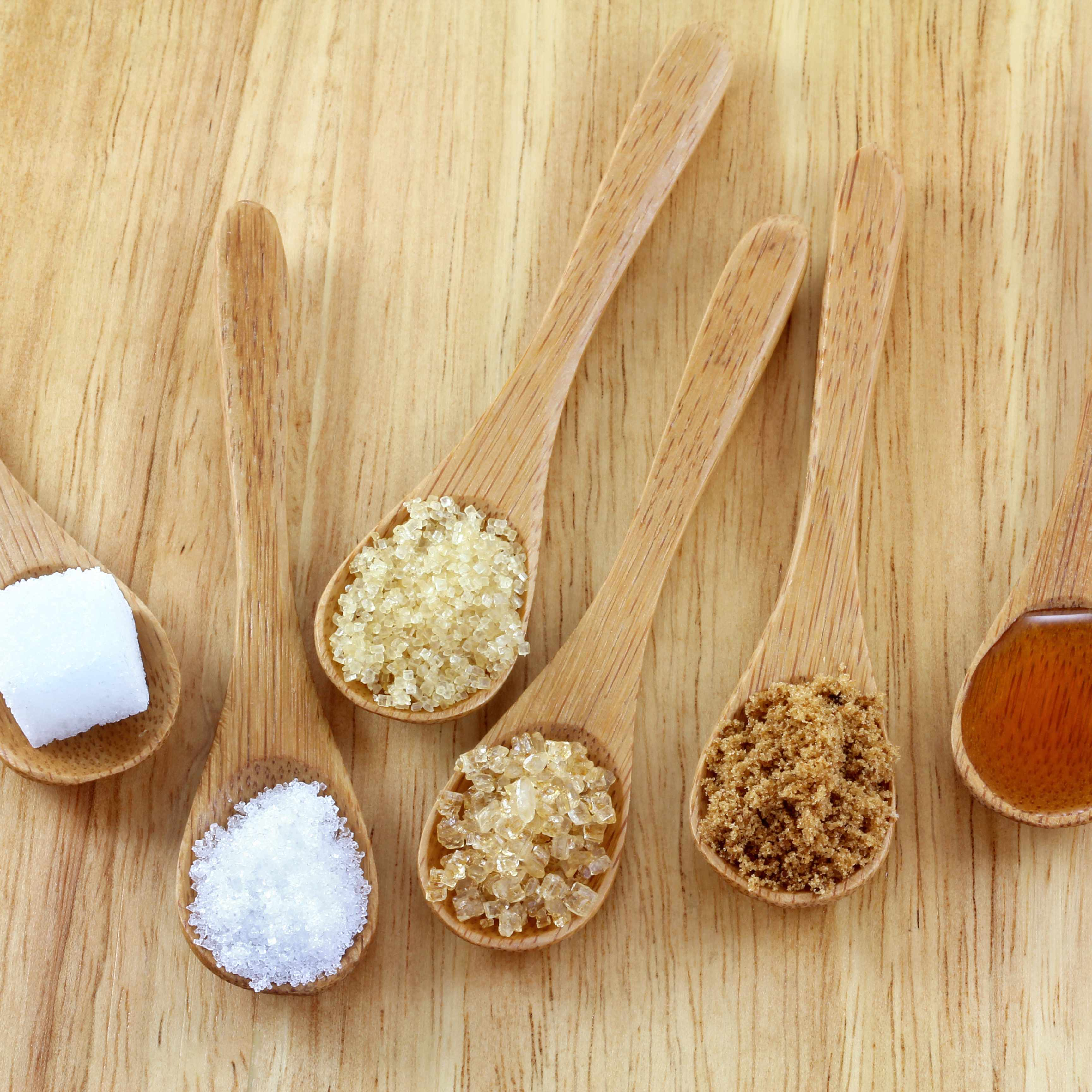 several wooden spoons full of different types of sugar, on a wooden tabletop