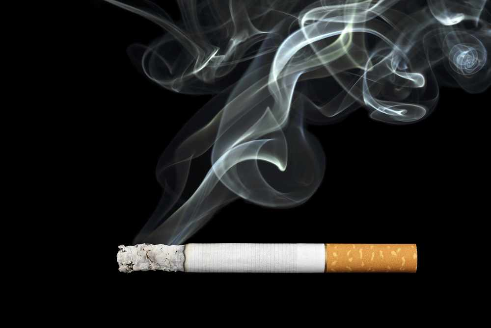 a burning cigarette, with smoke curling upward into the air