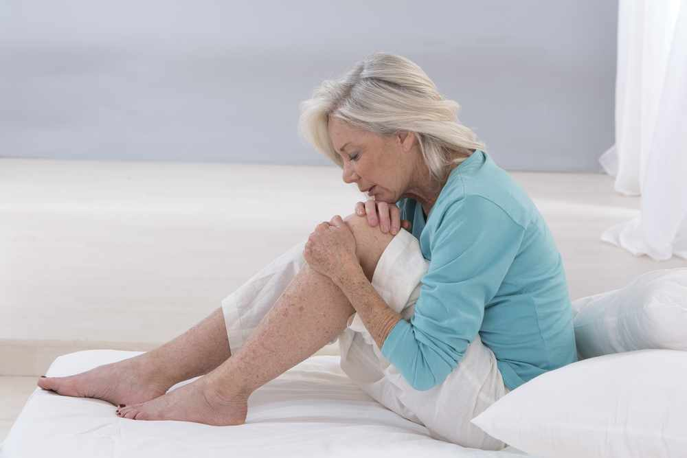 an older woman sitting on a bed, grimacing in pain and holding her knee