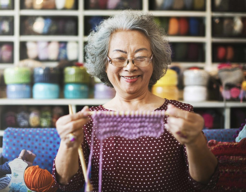 a smiling older woman holding up a knitting project, against a wall of yarn and craft supplies