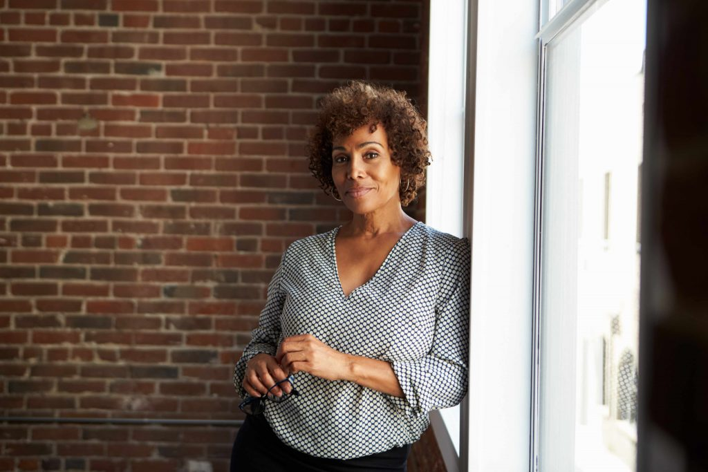 a middled aged African-American woman in casual business outfit, leaning against a window with brick wall in background