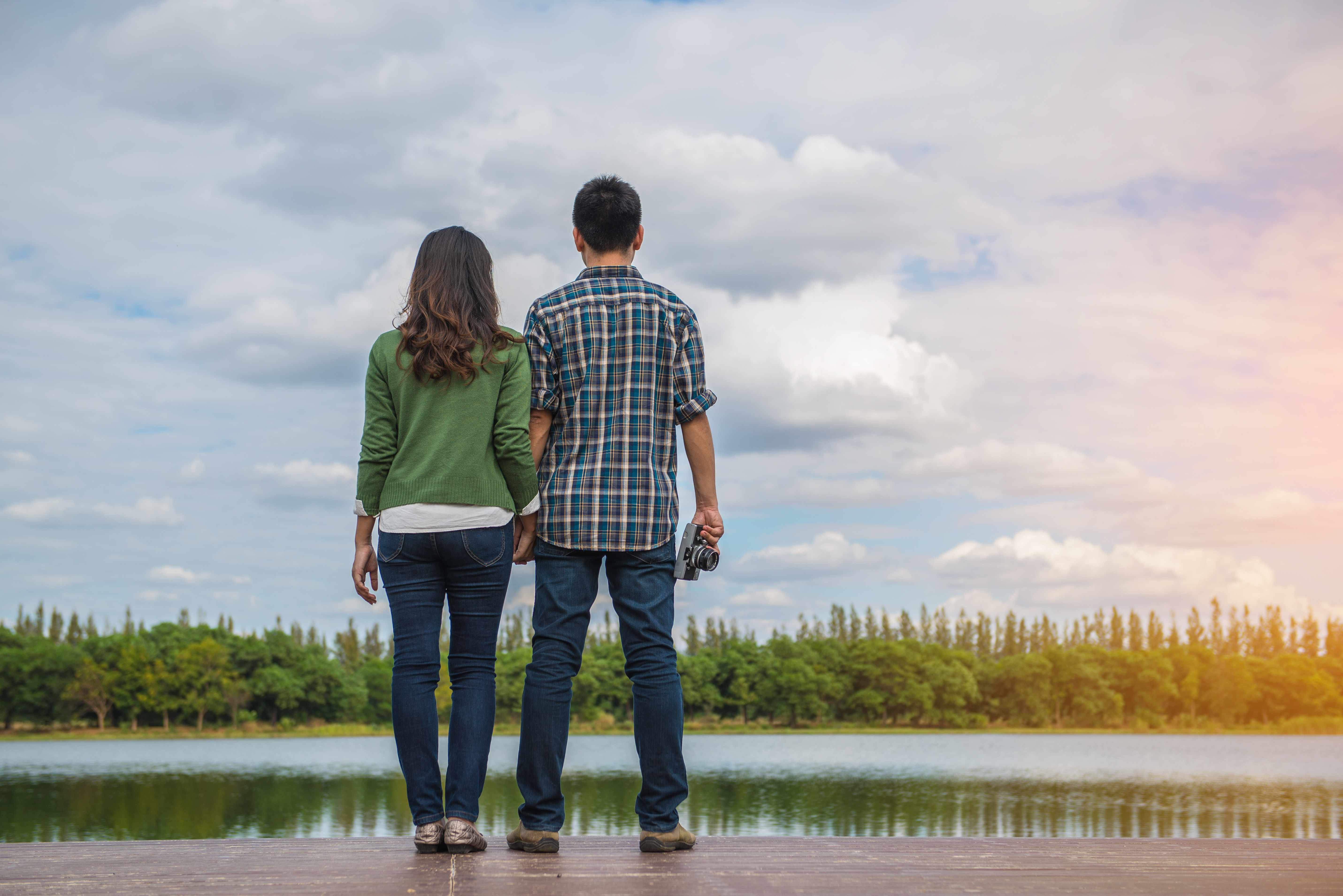 a couple standing on the edge of a lake looking at the landscape