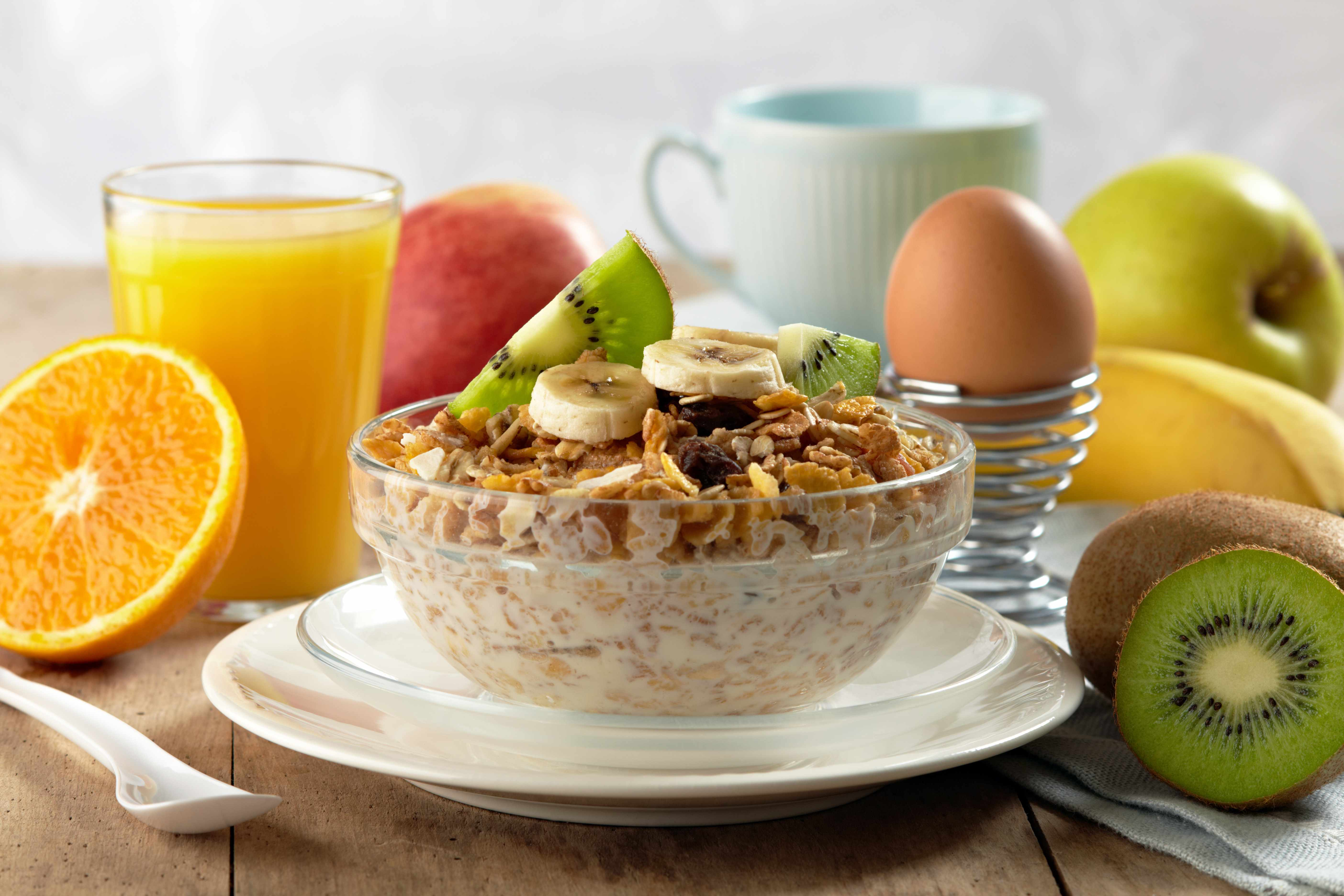 a nutritious, healthy breakfast with cereal, fruit, juice and an egg
