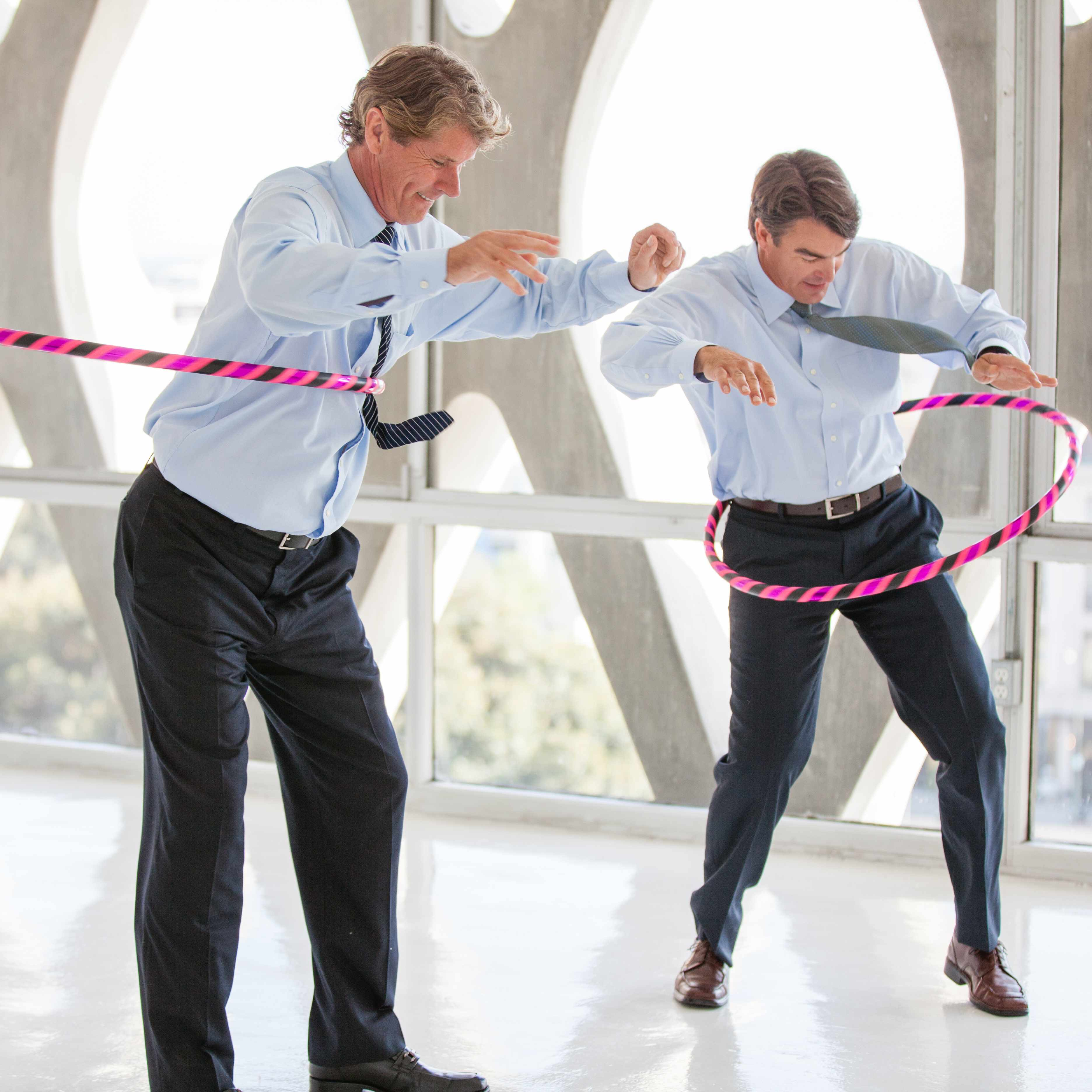 two men in suit pants, dress shirts and ties hula hooping