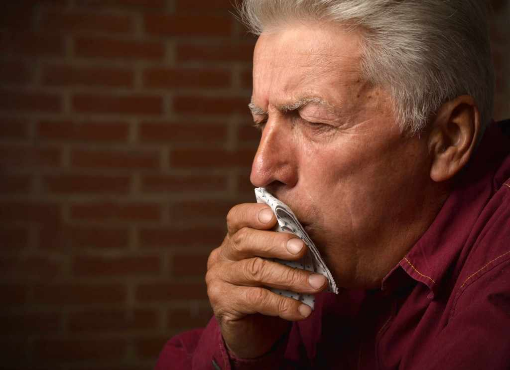 Elderly man coughing into a napkin