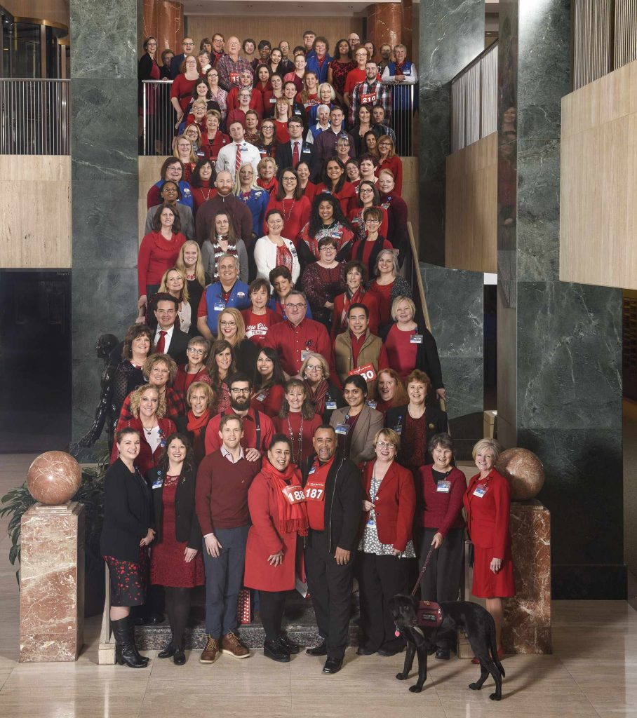 Mayo Clinic employees in red stand on staircase for a photo on National Wear Red Day