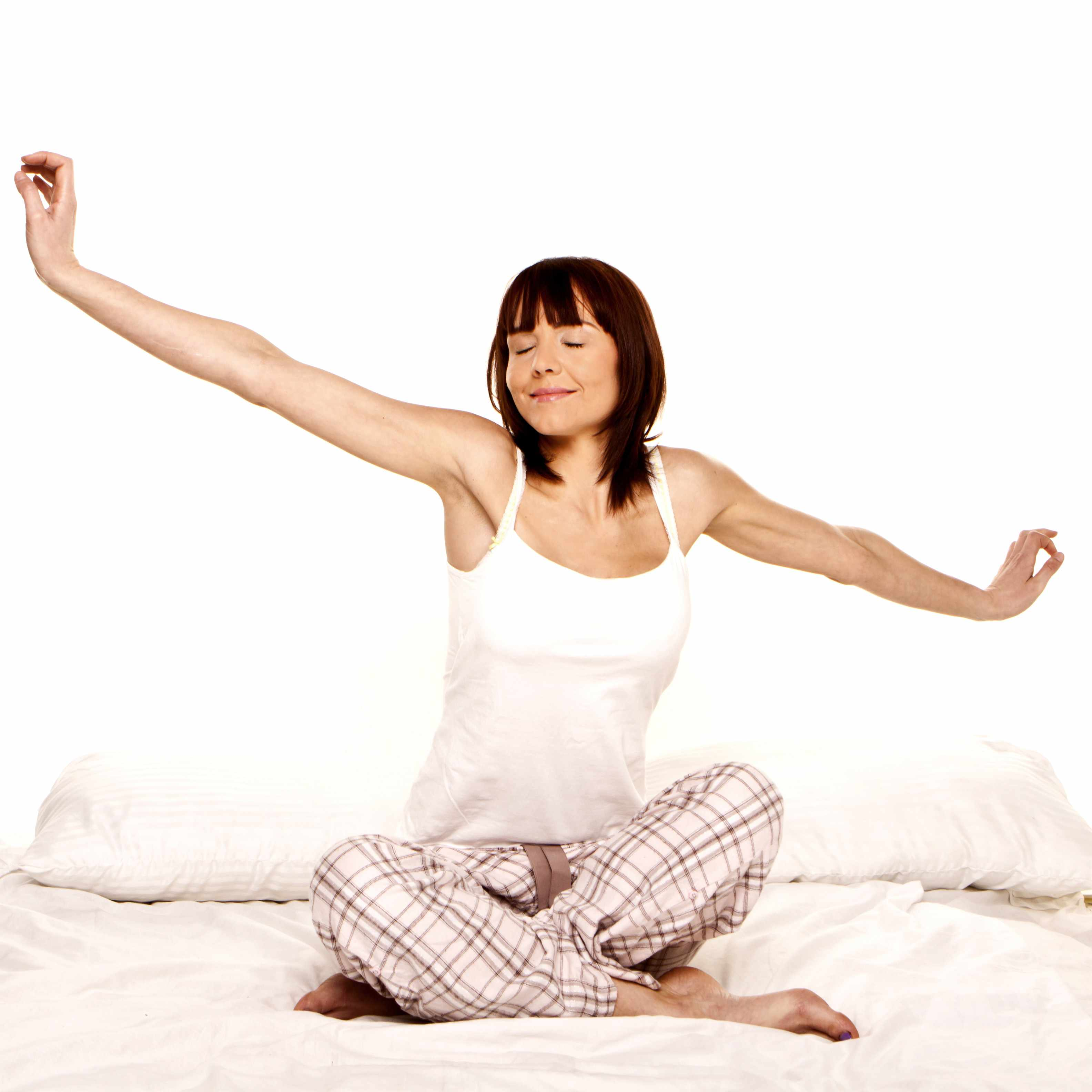 a young woman sitting on a bed in pajamas, smiling and stretching, waking up from a good night's sleep
