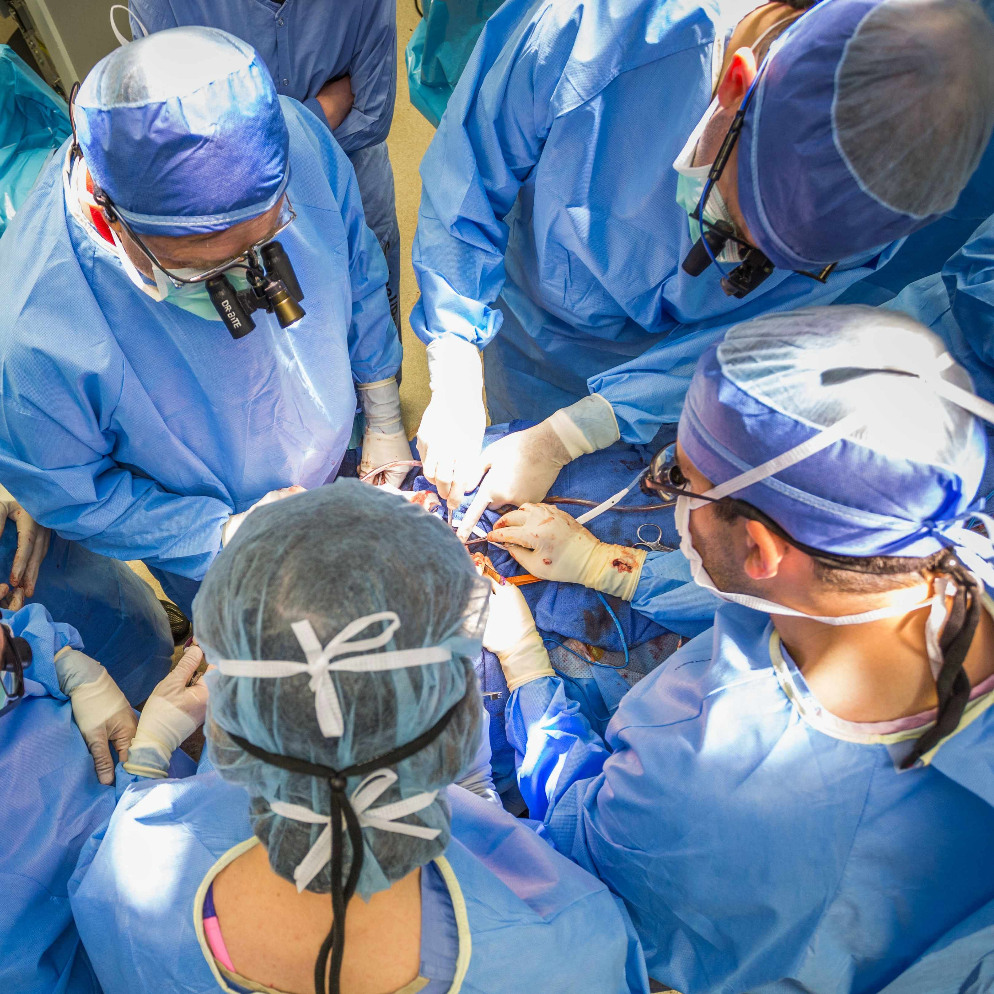 patient on operating table with surgeons surrounding patient