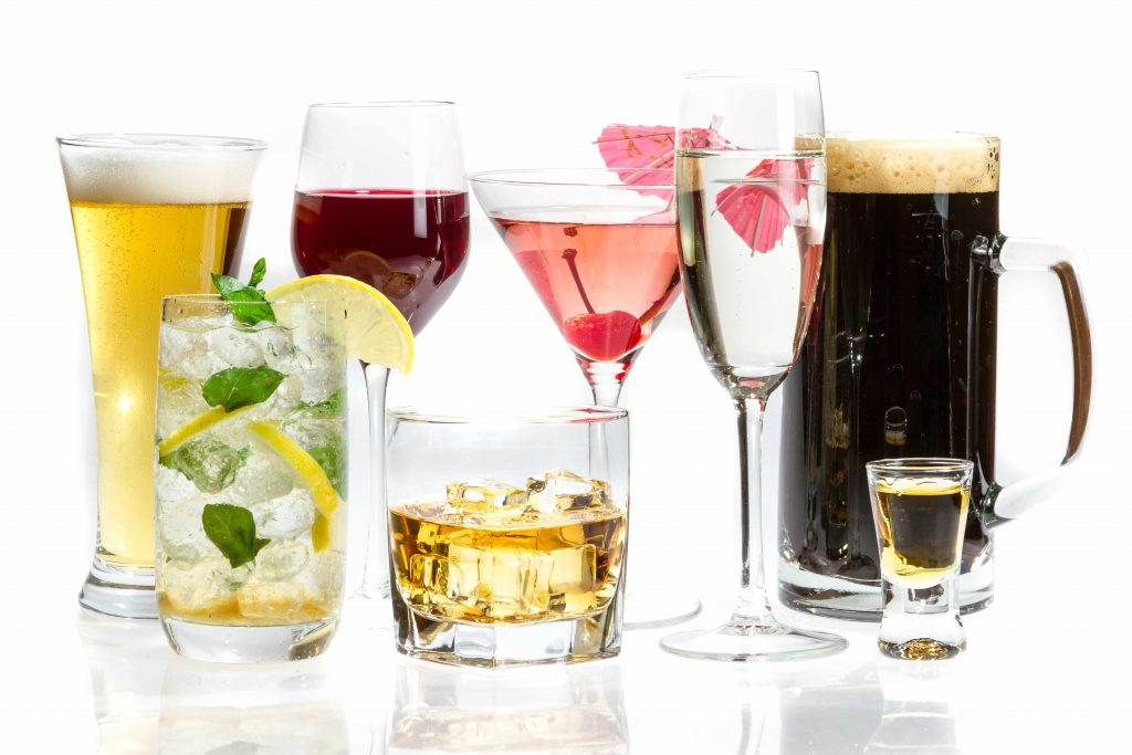 different kinds of alcoholic drinks in various glasses with a white background