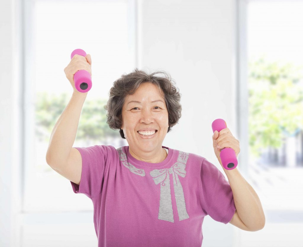 a smiling older woman, working out with hand weights