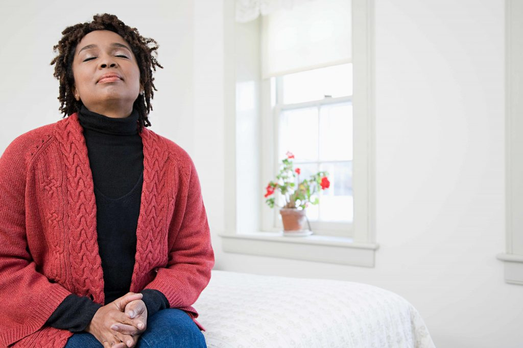 African-American woman sitting on edge of bed, eyes closed, resting and thinking