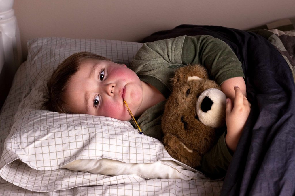 a sick little boy lying in bed, with red cheeks and a thermometer in his mouth, hugging a teddy bear