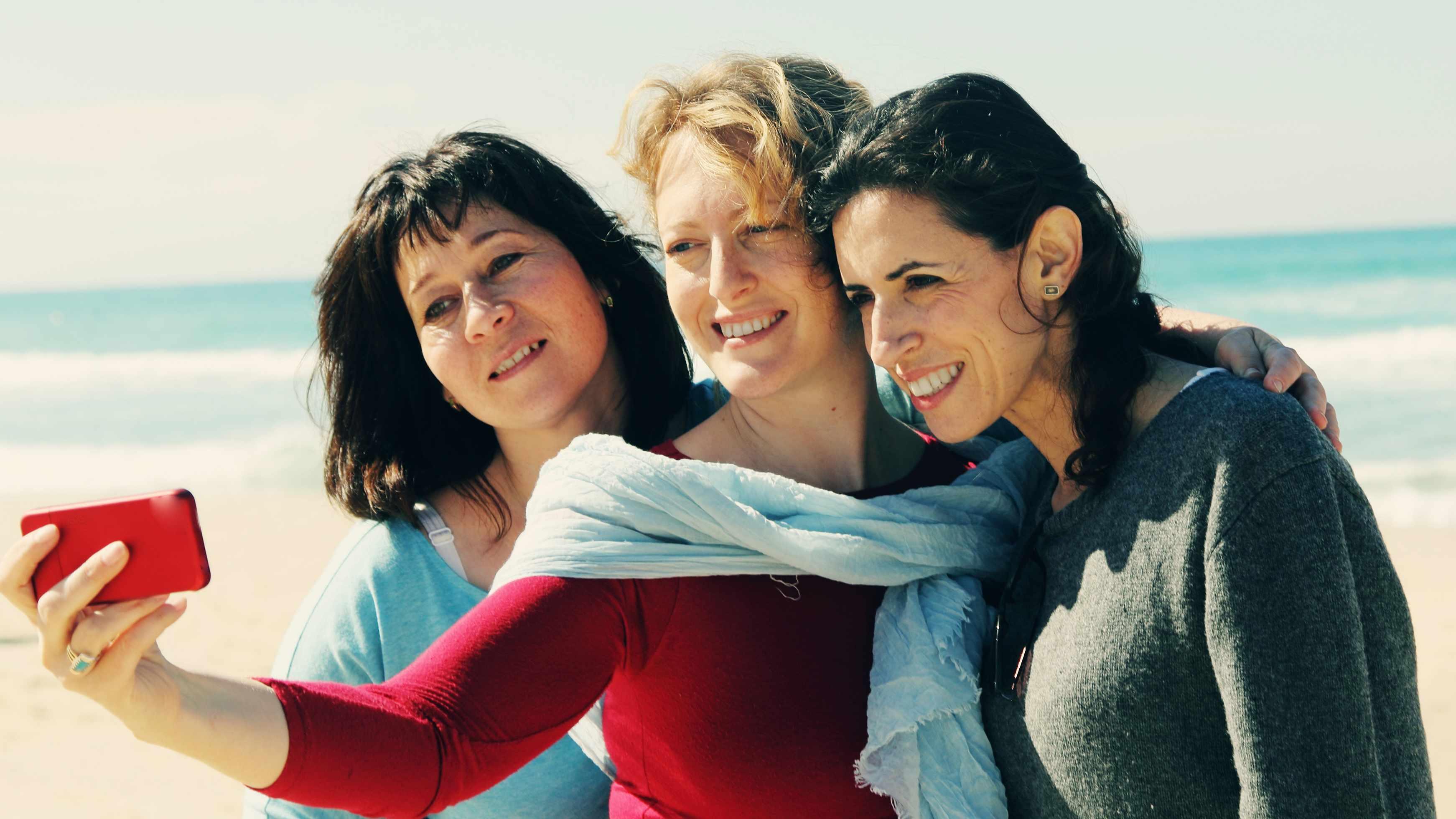 three middle-aged women friends walking on a beach taking a selfie