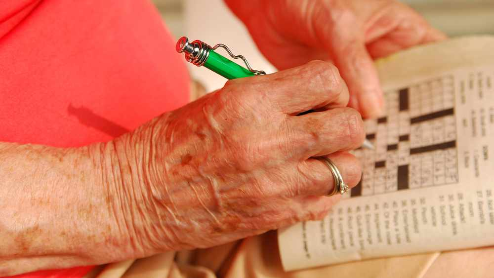 Acercamiento de la mano de una anciana sosteniendo un bolígrafo para hacer un crucigrama