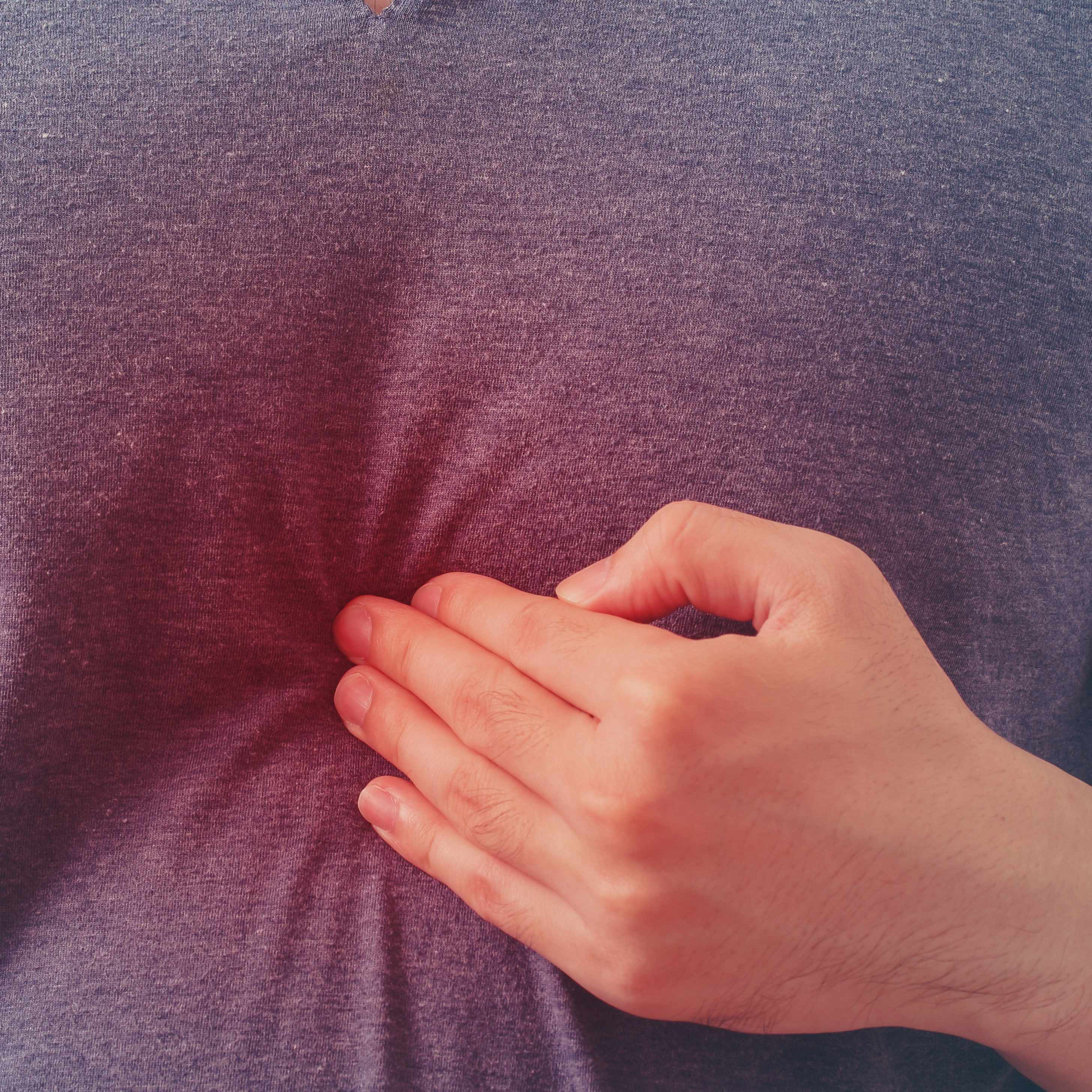 a man in pain pressing his chest with his hand indicating heartburn or heart attack