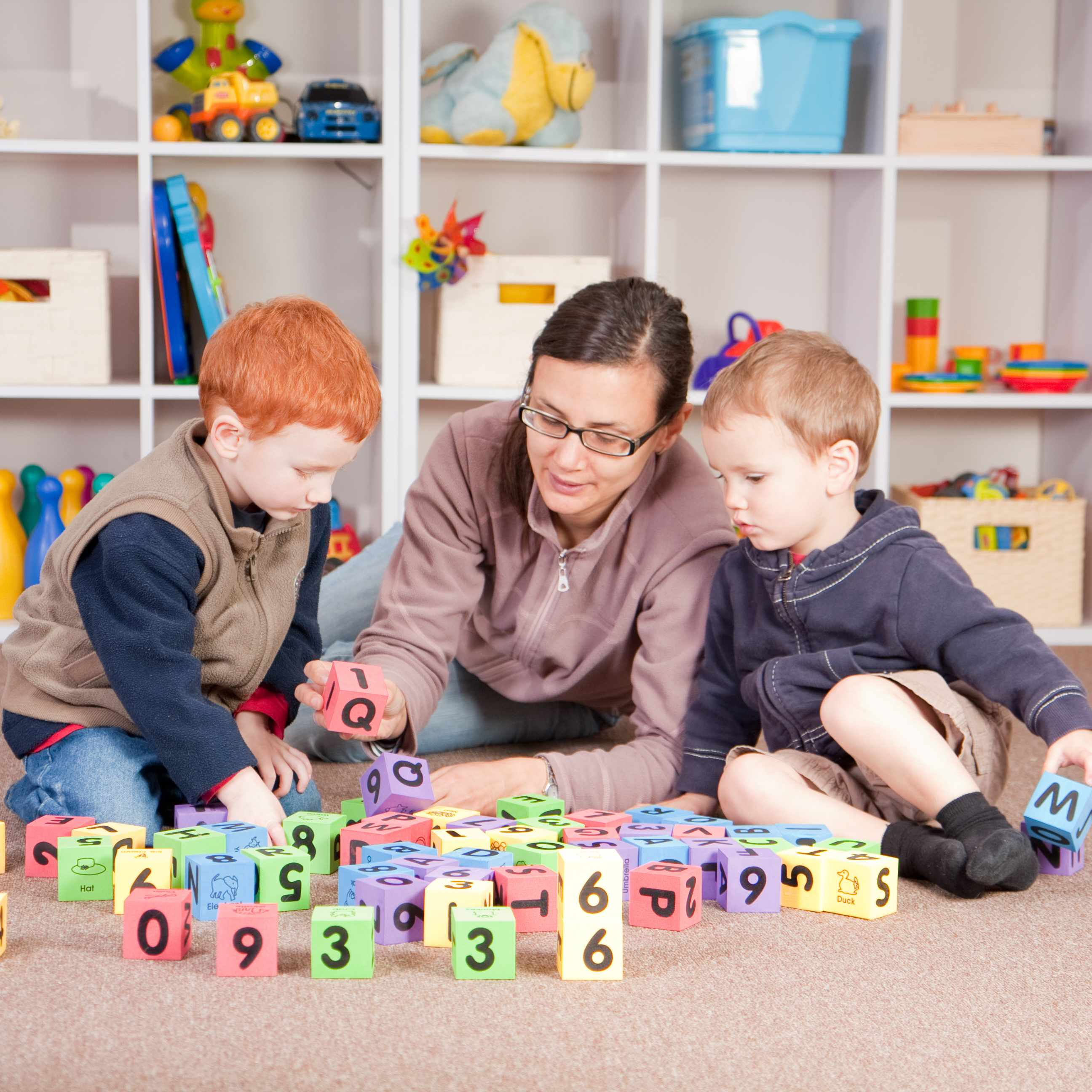 a mother and two young boys playing with blocks in a playroom, with orderly shelves of toys in the background
