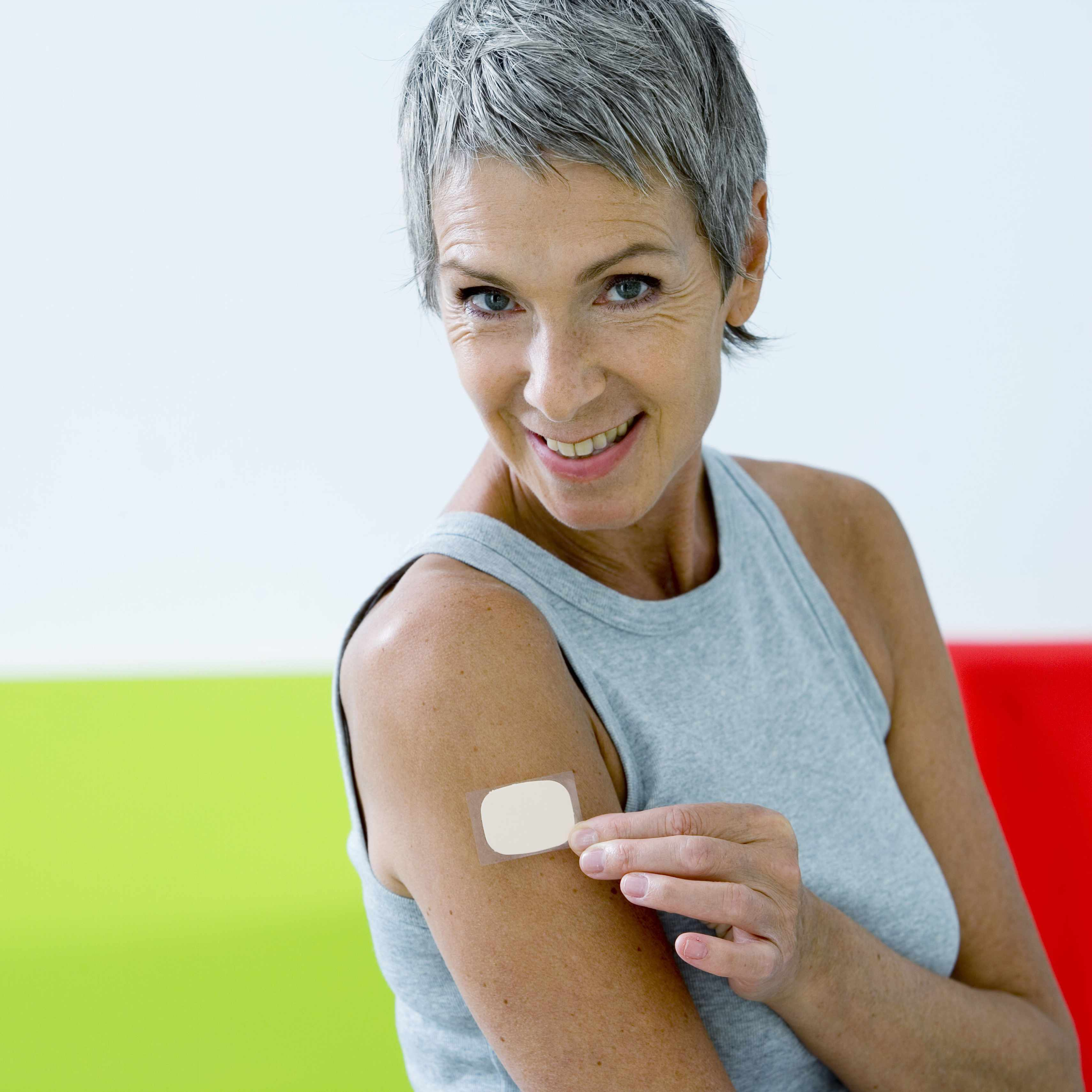 a smiling middle-aged woman with a nicotine patch on her upper arm