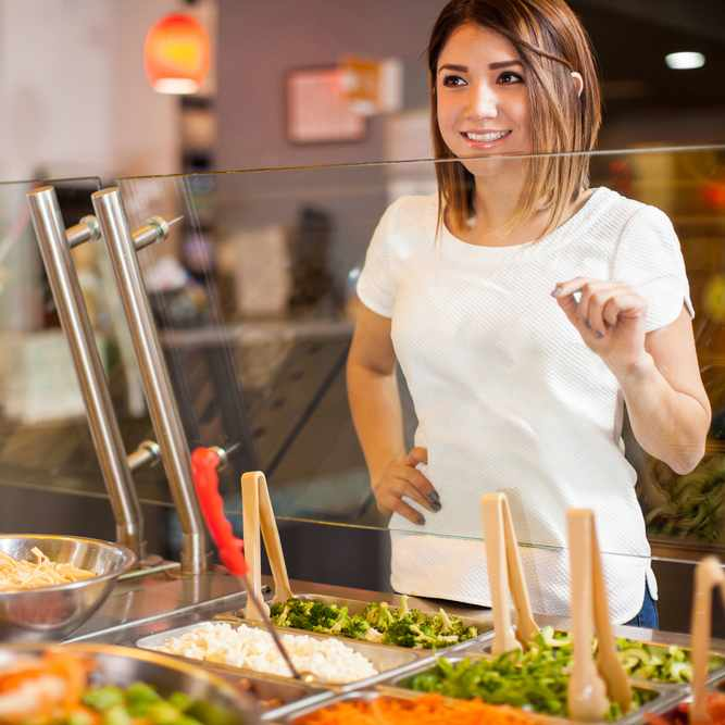 a smiling young woman choosing salad ingredients at a fast food restaurant