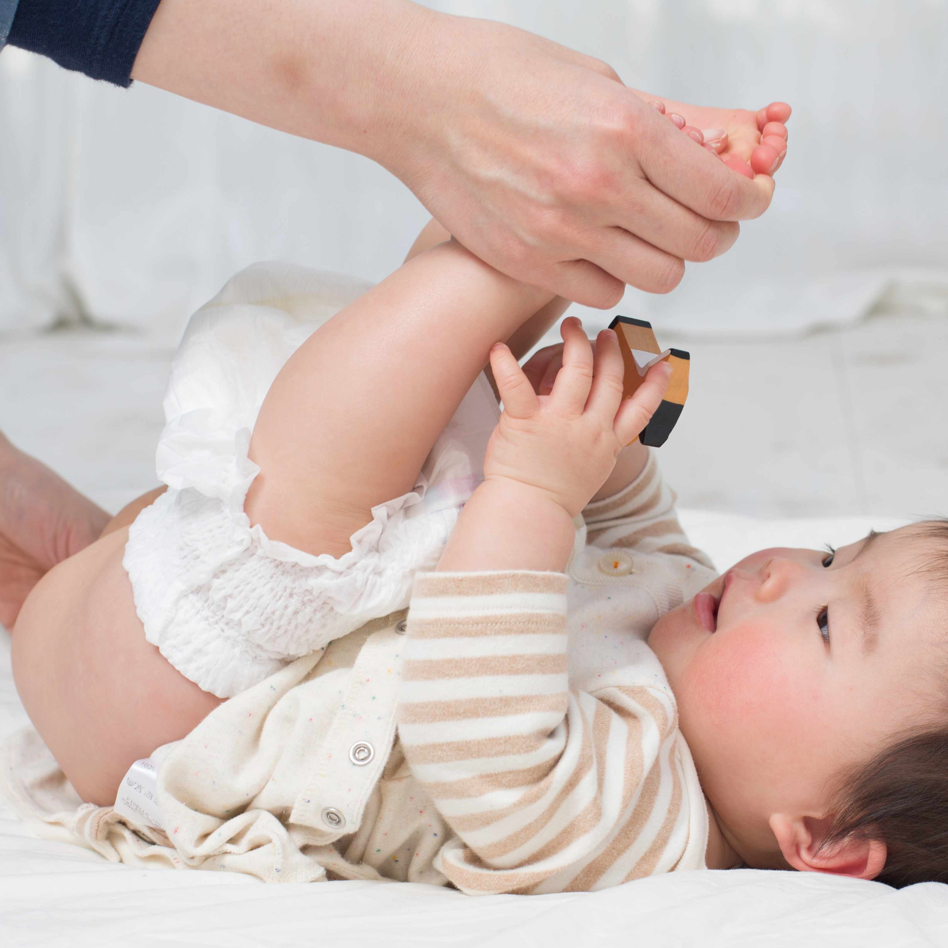baby on a table having diaper changed