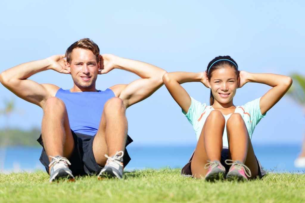 man and woman doing core workout exercises outside