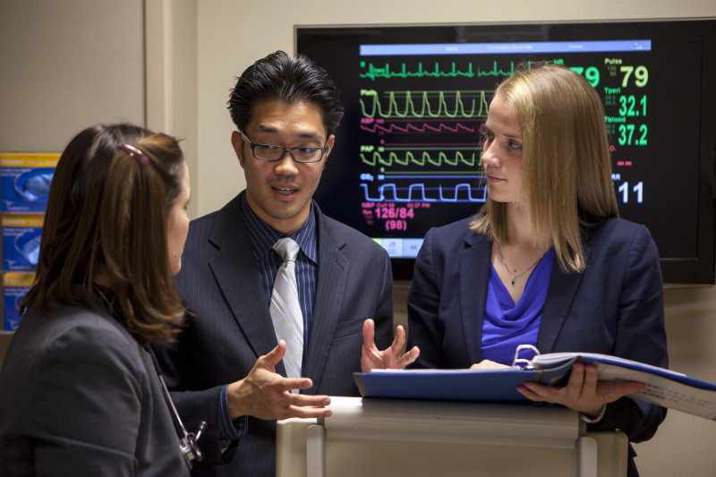 medical students consulting near EKG machine