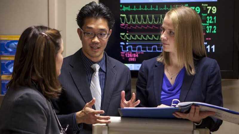 Estudiantes de medicina consultan entre ellos cerca de una máquina de ECG
